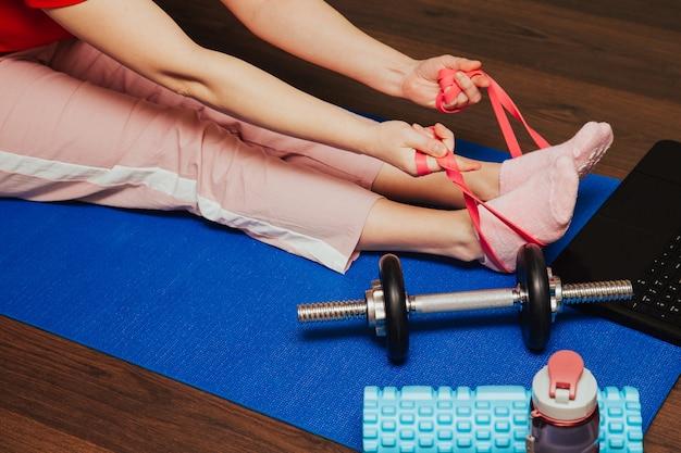 Blijf thuis. fitness thuis. vrouw die met rubberweerstandsband thuis uitoefenen