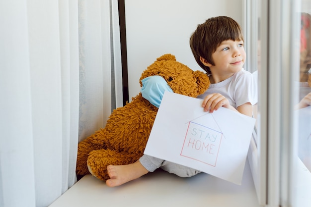 Blijf thuis in quarantaine voor de preventie van coronavirus-pandemieën. kind en zijn teddybeer, beiden in beschermende medische maskers, zitten op de vensterbank en kijken uit het raam