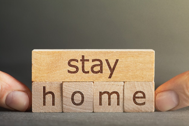 Blijf thuis inscriptie gegraveerd op blokken die vingers op een grijze achtergrond houden