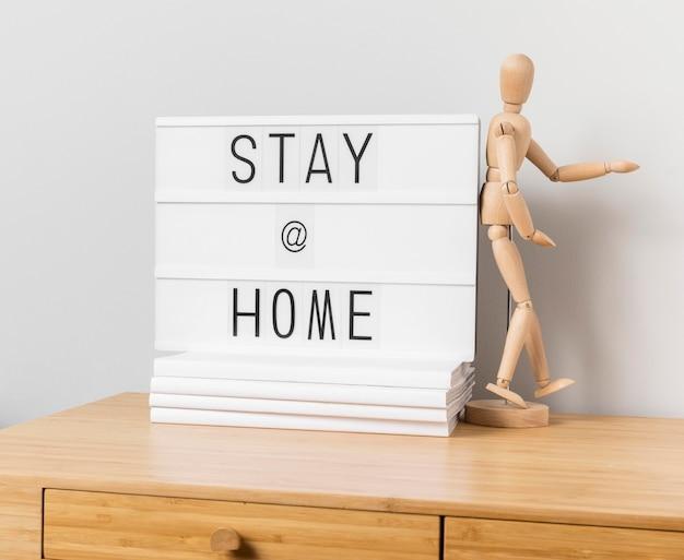 Blijf thuis inscriptie met houten mannequin