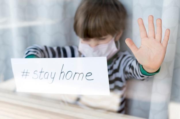 Blijf thuis kind draagt een masker