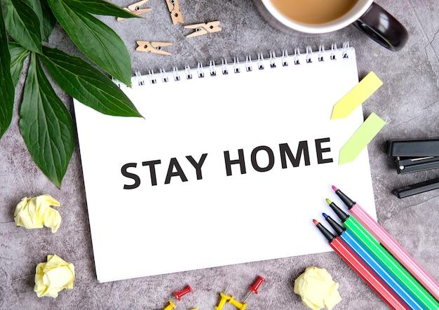 Blijf thuis op een notitieboekje met een kopje koffie, samengeperste vellen, kleurpotloden en nietmachine