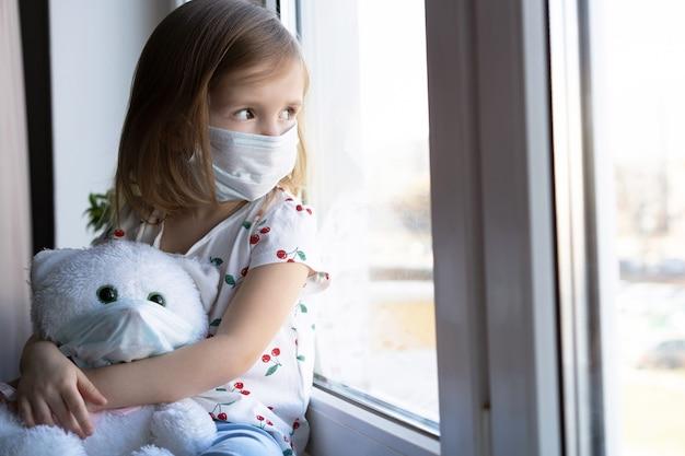 Blijf thuis quarantaine coronavirus pandemie preventie. verdrietig kind en zijn teddybeer beide in beschermende medische maskers zit op de vensterbank en kijkt uit het raam