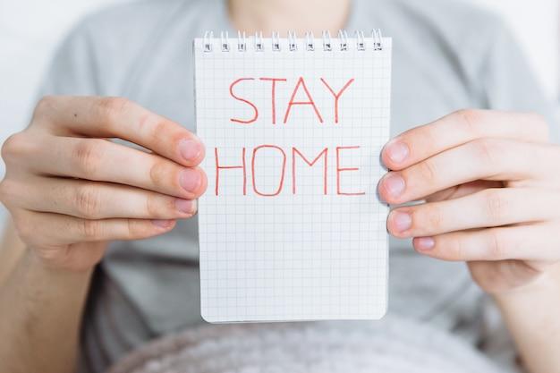 Blijf thuis schrijven op een notitieblok, epidemie van de ziekte coronavirus