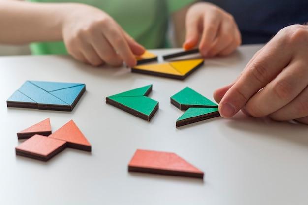Blijf thuis, sociale afstand en zelfisolatie tijdens quarantaineconcept. familie-vrije tijd. vader en zoon spelen logische spelletjes en houten puzzels.