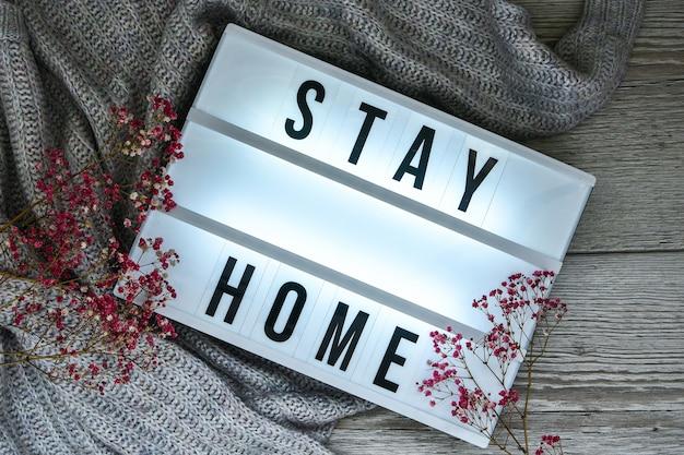Blijf thuis. tekst in je lichtbak, met een achtergrond van trui en droogbloemendecoratie. coronavirus-apparaten. social distancing. bescherming tegen pandemieën. witte lichtbak.