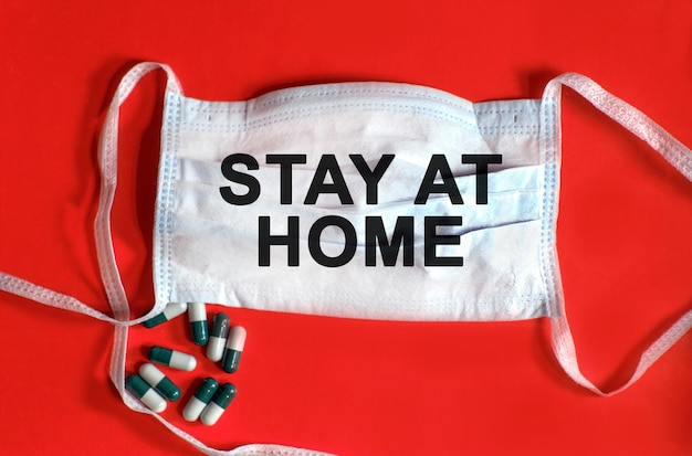 Blijf thuis - tekst op een beschermend gezichtsmasker, tabletten op een rode achtergrond
