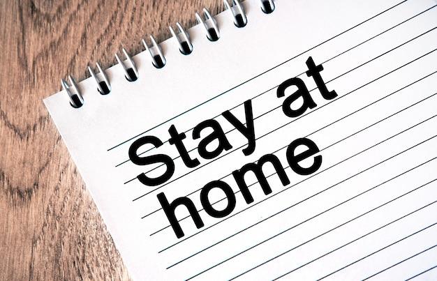 Blijf thuis - tekst op een wit notitieboekje, houten achtergrond