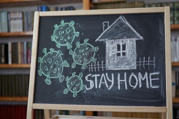 Blijf thuis. waarschuwing bij uitbraak. geschreven wit krijt op bord in verband met epidemie van coronavirus wereldwijd. covid 19 pandemische tekst op zwarte achtergrond met vrije ruimte. getekende virusbacteriën