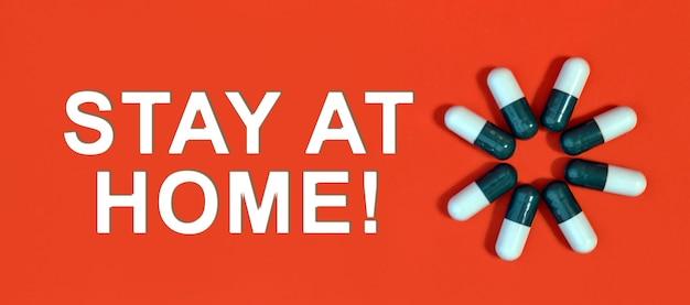 Blijf thuis - witte tekst op een rode achtergrond met pillencapsules