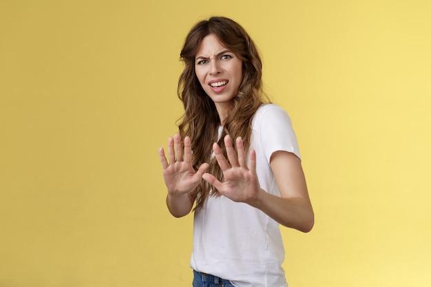 Blijf uit mijn buurt. teleurgesteld beledigd gehinderd joinge vrouw ineenkrimpen grimassen walging afkeer terughouden handen opsteken genoeg geen afwijzing gebaar weigeren fronsen gehinderd beledigd
