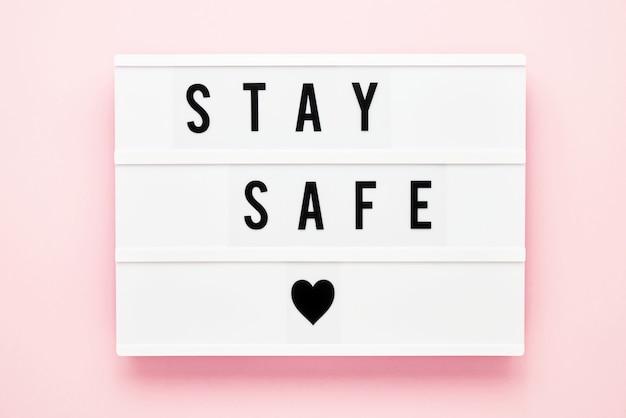 Blijf veilig geschreven in lichtbak op roze achtergrond. gezondheidszorg en medisch concept. bovenaanzicht. quarantaine concept.