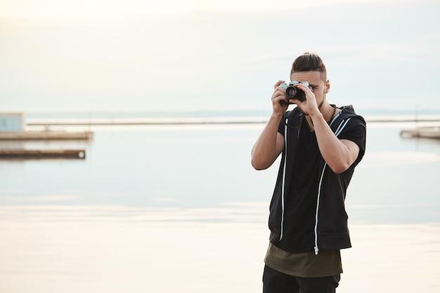 Blijf waar je bent, deze foto is geweldig. portret van creatieve knappe freelance fotograaf die door camera kijkt terwijl het nemen van beelden van aard en mensen, die zich dichtbij kust bevindt