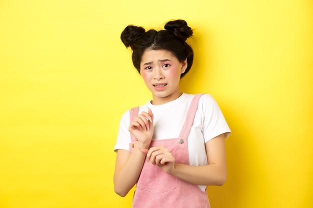 Blijf weg. het schuchtere, verlegen aziatische meisje doet een stap achteruit, steekt zijn handen op om iets walgelijks te blokkeren, grimassen ontevreden, nee zeggen, afwijzend met afkeer, geel.