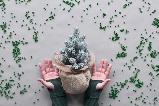 Blijf zo lang mogelijk je nep-kerstboom gebruiken. alternatieve groene eco vriendelijke kerst concept. handen tonen plastic boom verpakt in jute met plastic verspreid over ambachtelijk papier.