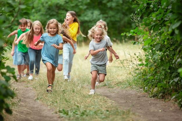 Blijheid. kinderen, kinderen die op groen bos rennen. vrolijke en gelukkige jongens en meisjes spelen, lachen, rennen door groene bloeiende weide. jeugd en zomer, oprechte emoties concept.