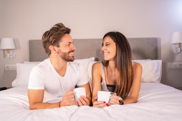 Blik van een verliefd stel in pyjama aan het ontbijten in het hotelbed, levensstijl van een verliefd stel