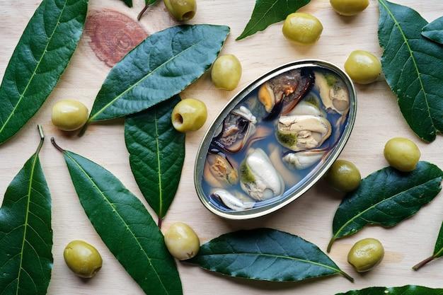 Blikje mosselen van boven gezien met olijven en laurierblaadjes