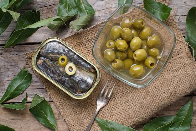 Blikje sardines in olijfolie en olijven op zak, bovenaanzicht