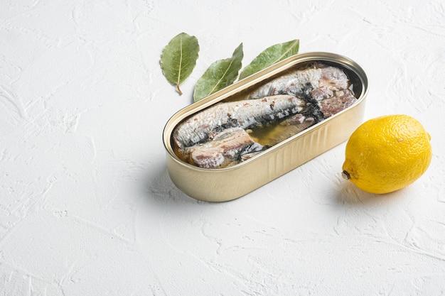 Blikje sardines in olijfolie set, op witte stenen tafel achtergrond, met kopie ruimte voor tekst