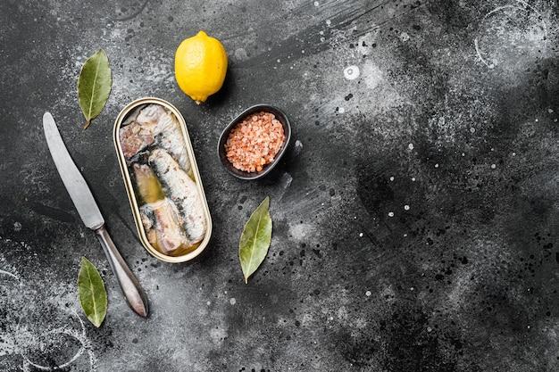 Blikje sardines in olijfolie set, op zwarte donkere stenen tafel achtergrond, bovenaanzicht plat lag, met kopieerruimte voor tekst