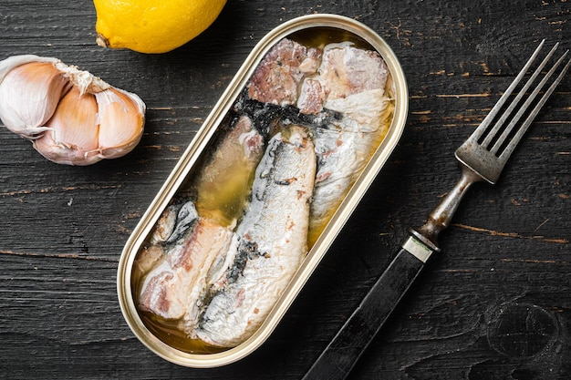 Blikje sardines in olijfolie set, op zwarte houten tafel achtergrond, bovenaanzicht plat lag Premium Foto
