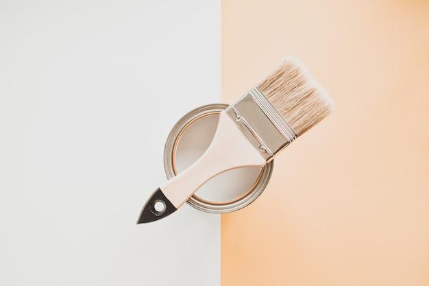 Blikje witte verf met een penseel, op een lichte achtergrond.