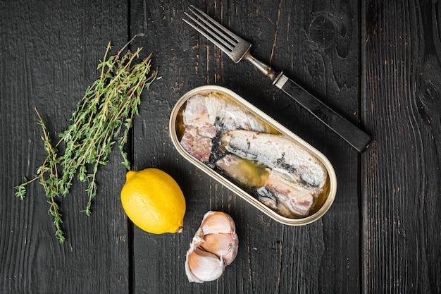 Blikje zeevruchten sardines vis set, op zwarte houten tafel achtergrond, bovenaanzicht plat lag