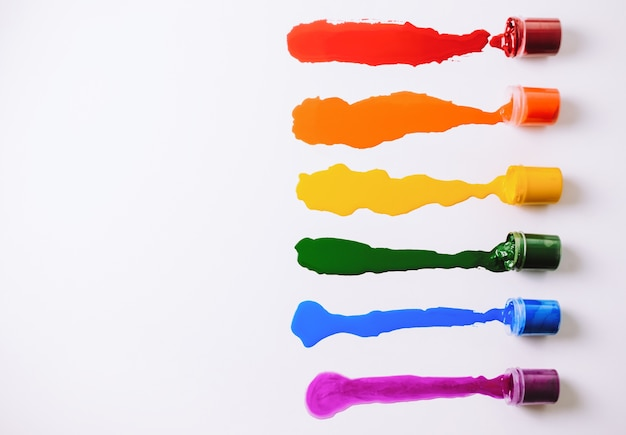 Blikken met gemorste verf van verschillende kleuren op een witte tafel.