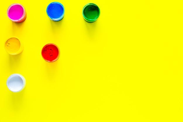 Blikken veelkleurige verf zijn gerangschikt in een driehoek in de bovenhoek van de foto op een gele b...