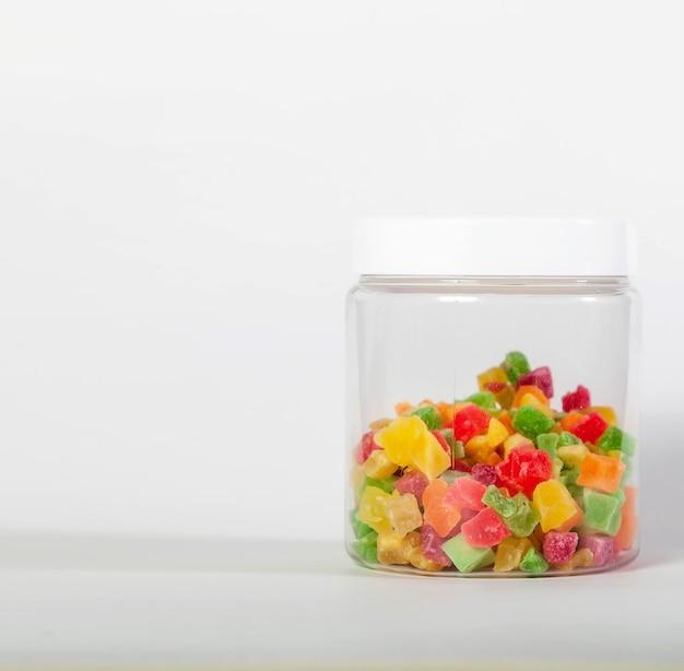 Blikken voor het opslaan van bulkproducten met gedroogde abrikoos op een witte geïsoleerde achtergrond. transparante plastic container met deksel voor het bewaren van voedsel en bulkproducten. abrikoos in pot voor winkel. ruimte kopiëren