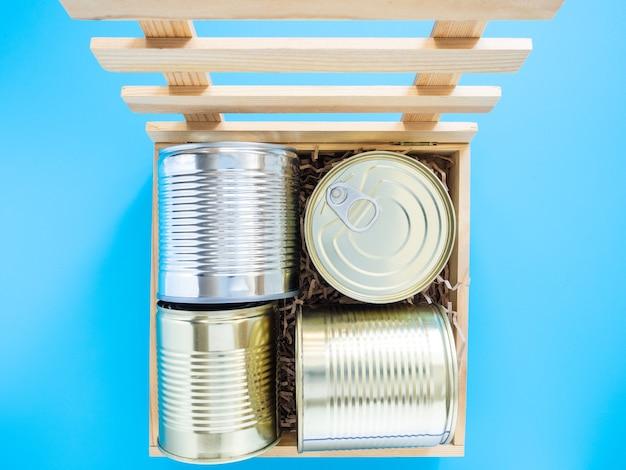 Blikken zijn verpakt in een houten kist met een zachte achterkant, isoleren op een blauwe achtergrond, close-up, mockup. concept van voedsel of cadeau tijdens quarantaine. een doos met voedseldonaties, eten bezorgen.
