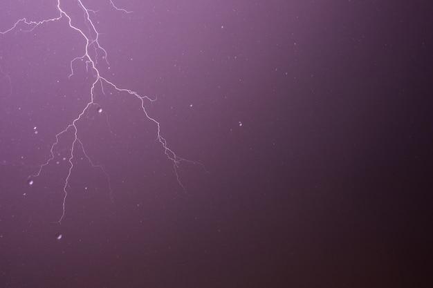 Bliksem en onweer op paarse hemelachtergrond met regendruppels.