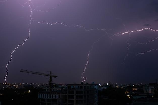 Bliksem en onweer over de stad 's nachts op donkere hemelachtergrond.