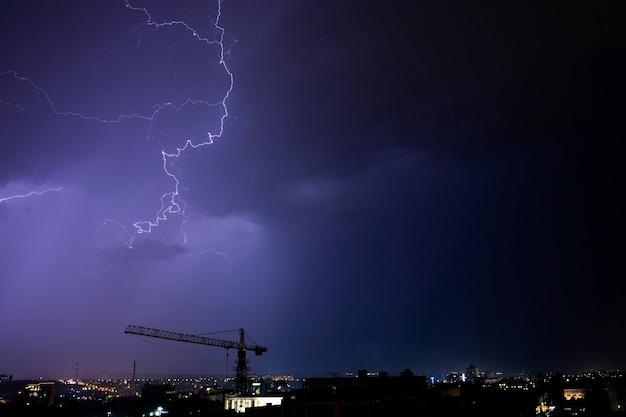 Bliksem en onweer over de stad 's nachts.