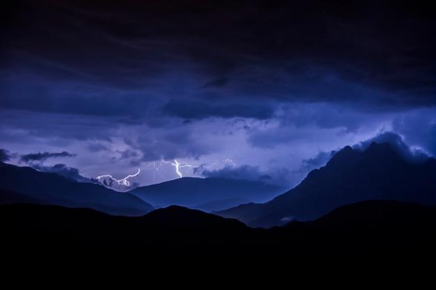 Bliksem en onweerswolken in de nacht over bergen