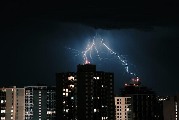 Bliksem in de donkere lucht boven de gebouwen in de stad 's nachts