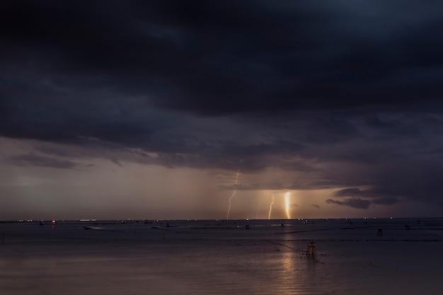 Bliksem in de zee de regenwolken vormen zich.