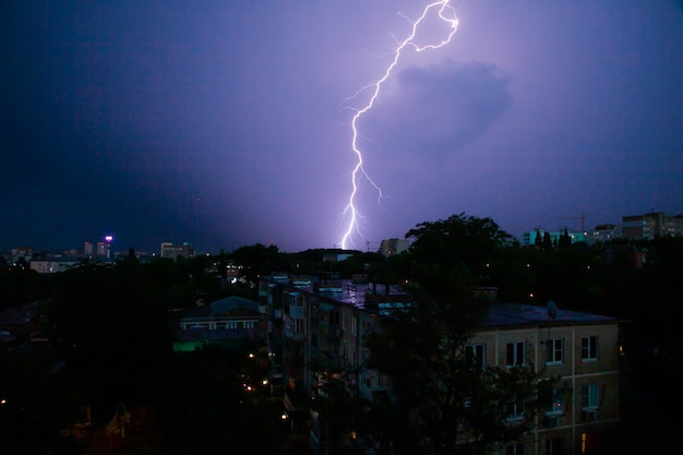 Bliksem onweer over de daken van de stad in de nachtelijke hemel