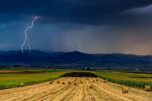 Bliksem over het veld. onweersbui en bliksem over het landbouwgebied.