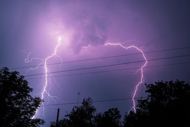 Blikseminslag over het huis en donkere stormachtige lucht op de achtergrond