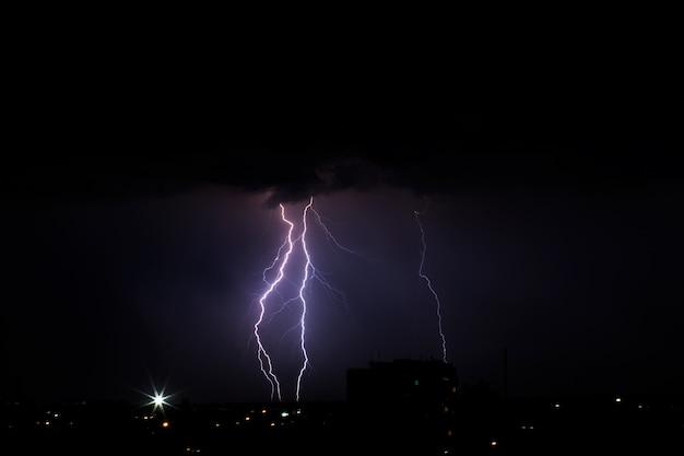 Bliksemweer over de stad in paars licht.