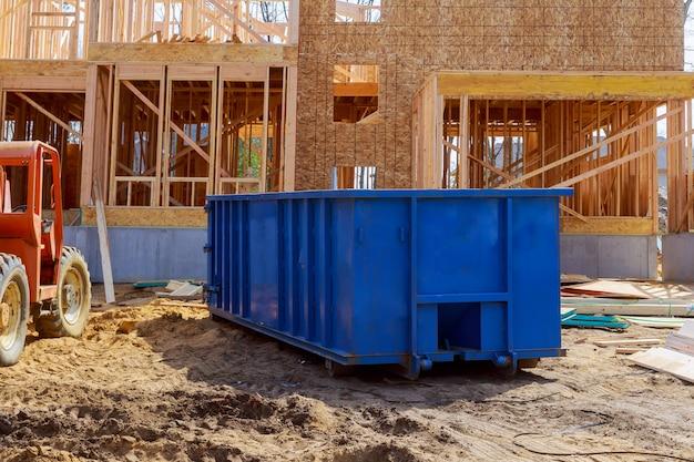 Blind afvalcontainer, recyclen afval en vuilnisbakken dichtbij nieuwe bouwwerf van de bouw van flatgebouwen