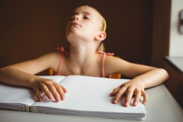 Blind meisje dat beide handen gebruikt om braille te lezen