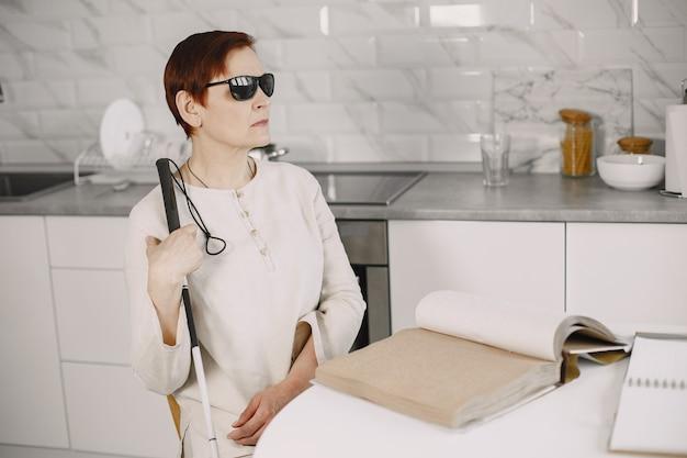 Blinde rijpe vrouw die thuis brailleboek leest
