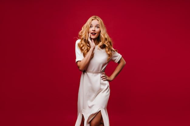 Blithesome betoverend meisje in witte jurk staande op rode muur. zorgeloze blonde vrouw die verbazing uitdrukt.