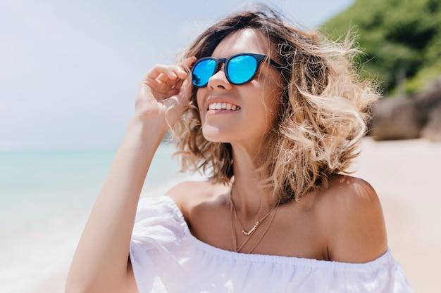 Blithesome blonde vrouw die in zonnebril hemel bekijkt. openluchtportret van betoverende kaukasische vrouw die aan zandstrand koelt.