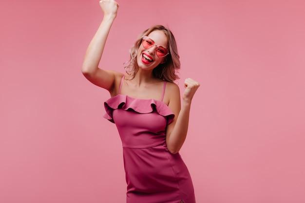 Blithesome europese jonge vrouw in zonnebril dansen op roze muur