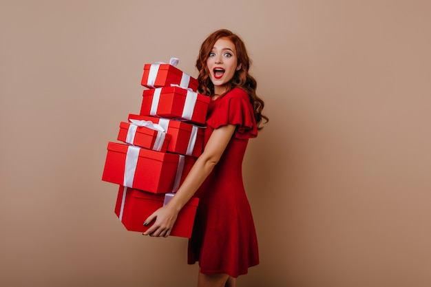 Blithesome feestvarken in jurk poseren met cadeautjes. blij jong vrouwelijk model met nieuwe jaargeschenken.
