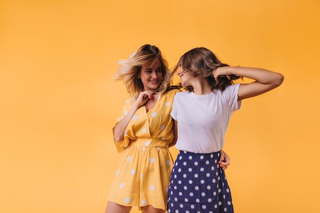 Blithesome jonge vrouw die in gele uitrusting vriend met glimlach bekijkt. blije kaukasische zusters die op sinaasappel koelen.